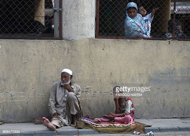 Pakistani woman looks at beggers sitting on a footpath near a market in Rawalpindi on September 21 2016 / AFP / FAROOQ NAEEM