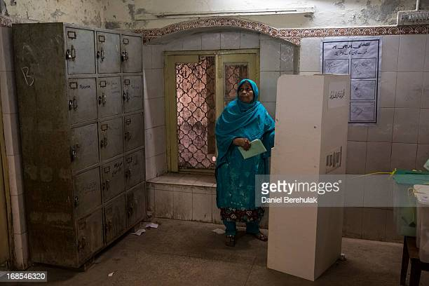 Pakistani woman looks on as she prepares to vote at a polling station on May 11 2013 in the old city of Lahore Pakistan Millions of Pakistanis cast...