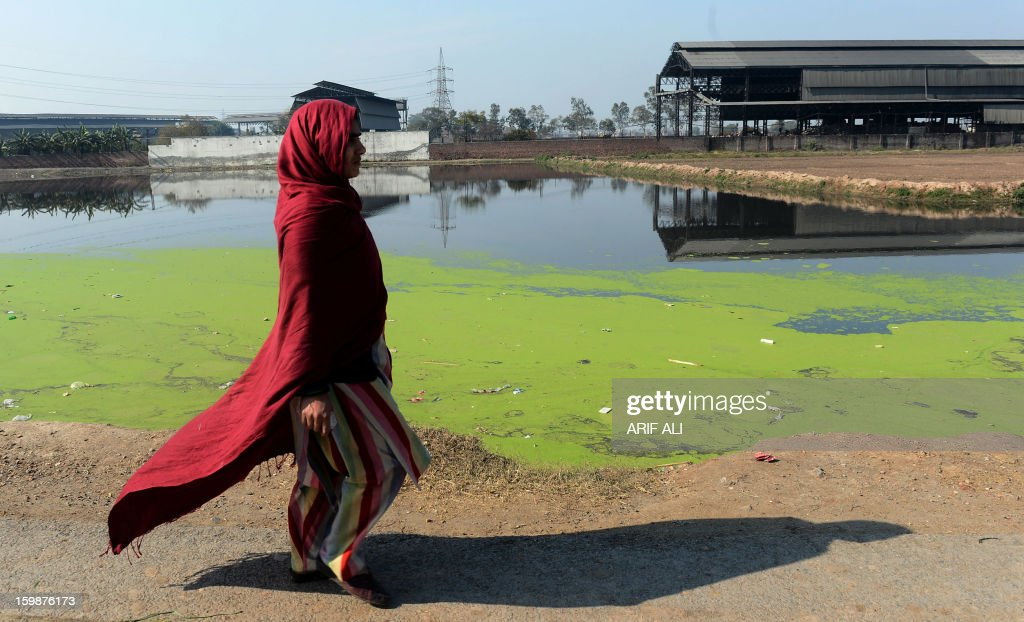 A Pakistani woman walks alongside a body of polluted waterin an industrial area of Lahore on January 22, 2013. AFP PHOTO/Arif ALI