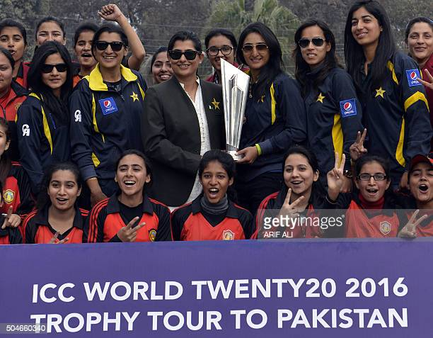 Pakistani women cricketers pose for a photograph with the ICC 2016 World Twenty20 trophy during a ceremony in Lahore on January 12 2016 The...