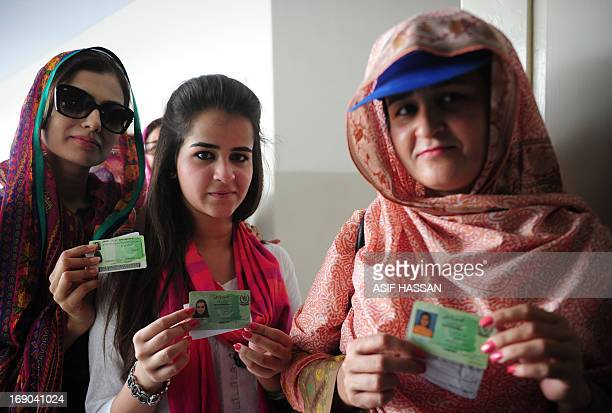 Pakistani women display their identity cards during the repoll of voters in the constituency known as NA250 in Karachi on May 19 2013 Hundreds of...