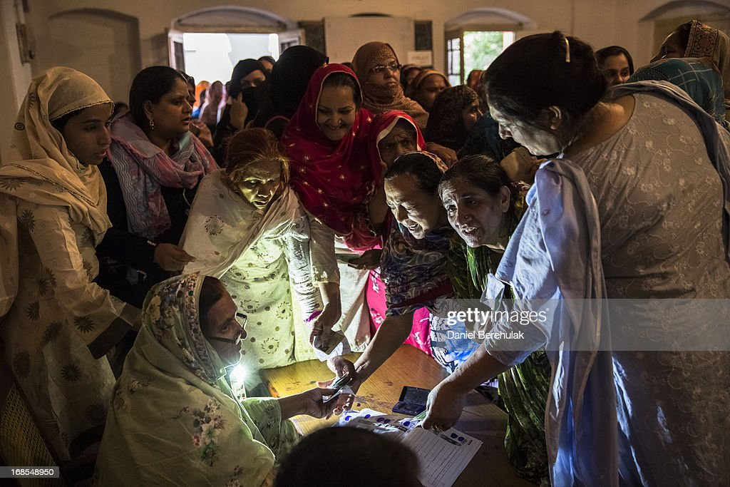Pakistani women jostle to receive their ballot papers prior to casting their ballot at a polling station on May 11, 2013 in the Old City of Lahore, Pakistan. Millions of Pakistanis cast their votes in parliamentary elections held today on May 11. It is the first time in the country's history that an elected government will hand over power to another elected government.