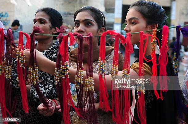 Pakistani women look at 'rakhi' at a roadside shop ahead of the Hindu festival Raksha Bandhan in Karachi on August 9 2014 The annual festival of...