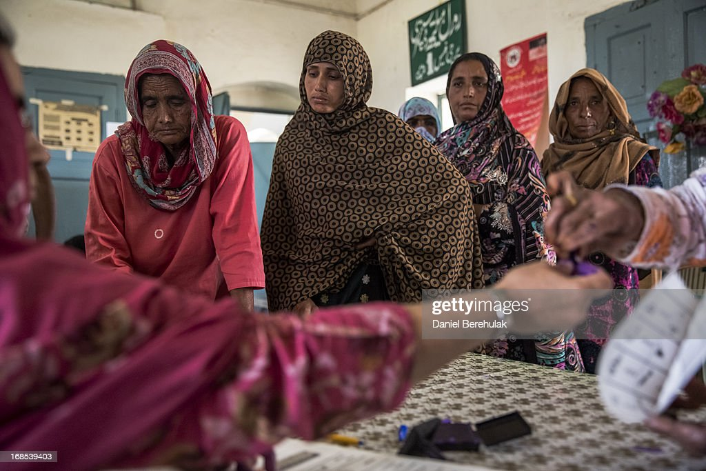 Pakistani women queue to cast their vota as another woman has her finger marked after having voted at a polling station on May 11, 2013 on the outskirts of Lahore, Pakistan. Millions of Pakistanis cast their votes in parliamentary elections held today on May 11. It is the first time in the country's history that an elected government will hand over power to another elected government.