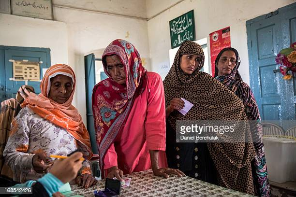 Pakistani women queue to cast their vote at a polling station on May 11 2013 on the outskirts of Lahore Pakistan Millions of Pakistanis cast their...