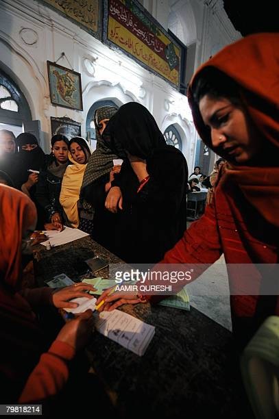 Pakistani women register with election officials prior to casting their ballots at a polling station in Rawalpindi on February 18 2008 as the nation...