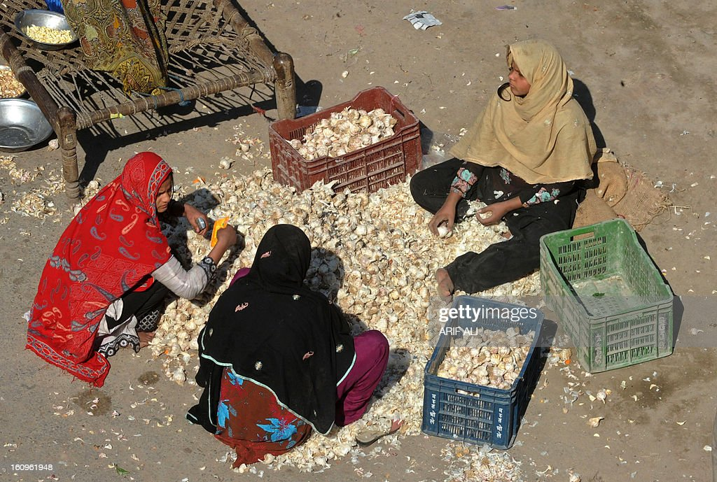Pakistani women sort garlic for sale at a market in Lahore on February 8, 2013. Pakistan's central bank on Friday kept its benchmark interest rate unchanged at 9.5 percent, as its foreign exchange reserves fell and GDP growth is expected to remain below four percent. AFP PHOTO/Arif ALI