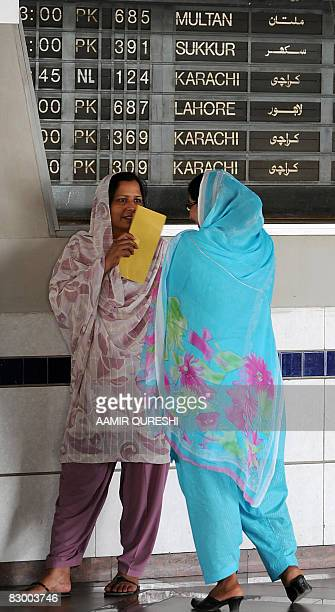 Pakistani women speak as they stand in front of an information board displaying information on delayed flights at Islamabad International Airport in...