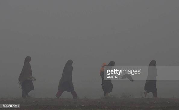Pakistani women walk along a street on a foggy day in Lahore on December 7 2015 Most areas of Punjab province face heavy fog causing traffic...