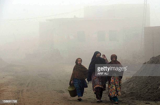 Pakistani women walk on a foggy street in Lahore on December 24 2012 The ongoing spell of dense fog and freezing weather conditions has continued to...