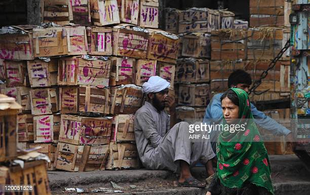 A Pakistani women walks past mango boxes in a truck at a vegetable market in Lahore on July 28 2011 Pakistani government statements that tax receipts...