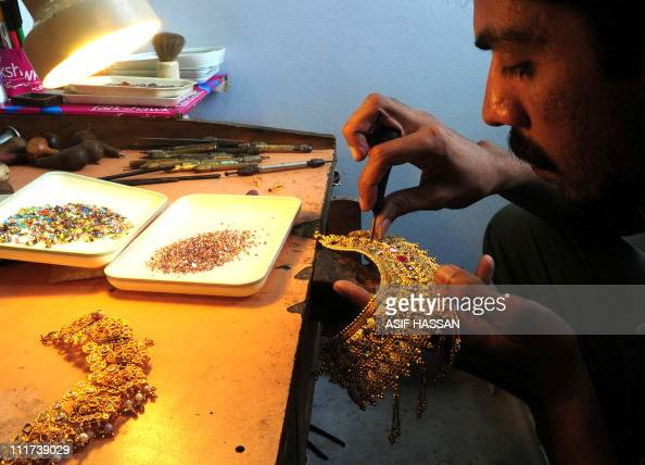 A Pakistani worker prepares a necklace at his gold workshop in Karachi on April 6 2011 The gold prices have touched a historic high with 46650...