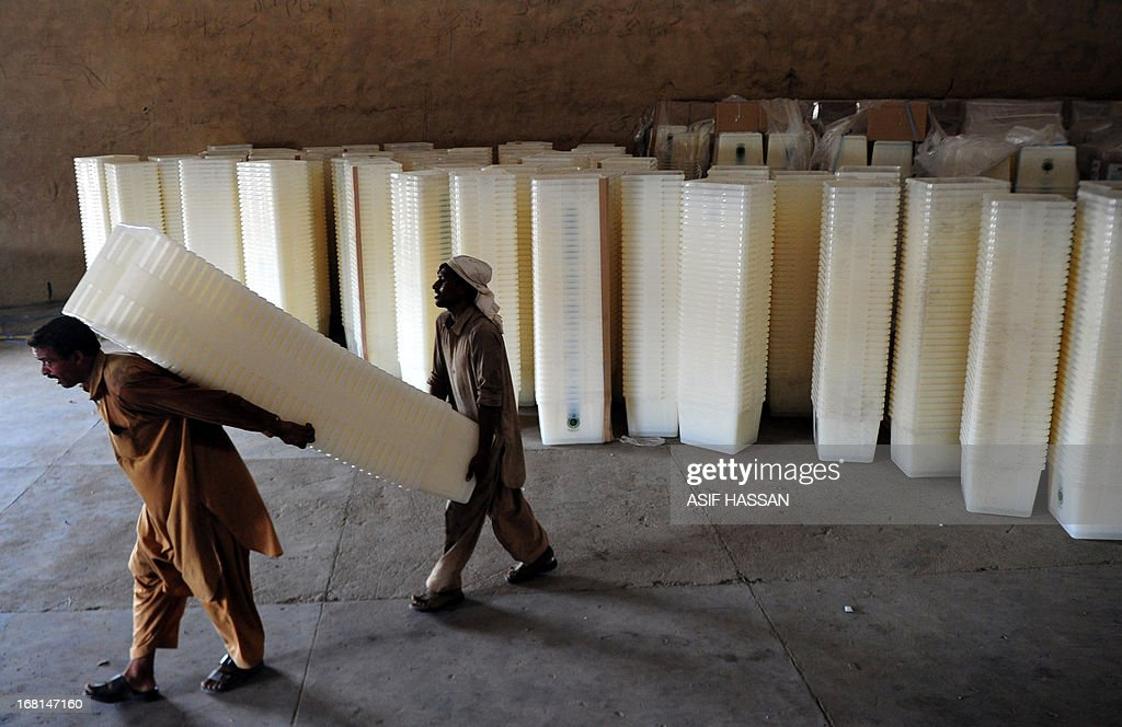 Pakistani workers carry ballot boxes to be transported to polling stations for the forthcoming parliamentary elections, in Karachi on May 6, 2013. Pakistan will elect its new government for the next five years in polls on May 11. The election of the national and four provincial assemblies will mark the first time a civilian government has completed a full term and handed over to another, in a country that has been ruled by the military for half its existence.