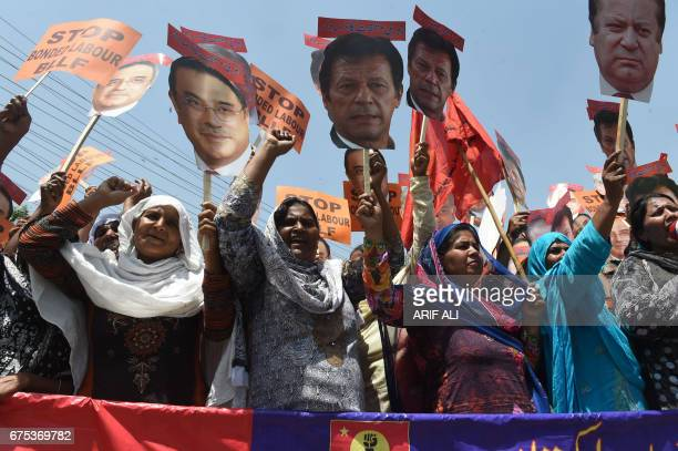 Pakistani workers carry cutouts of images of Pakistani political parties leaders as they shout slogans during a May Day rally to mark International...