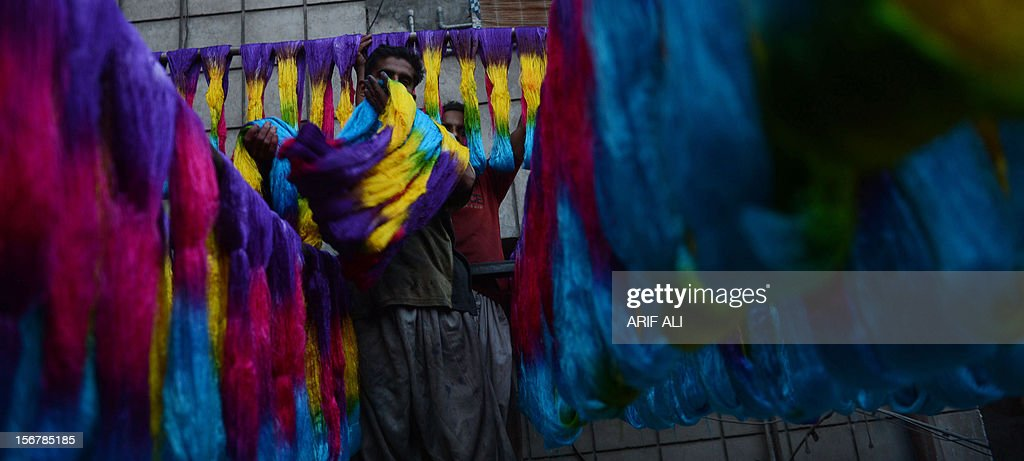 Pakistani workers dry thread after dyeing at a factory in Lahore on November 20, 2012. The country is the world's fourth-largest producer of cloth and the industry accounts for 60 percent of export revenue according to official data. But shortages are heaping pressure on Pakistan's crippled and debt-ridden economy. AFP PHOTO/Arif ALI