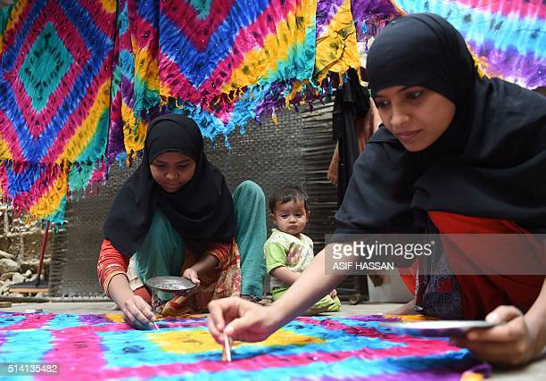 Pakistani workers dye scarves at their home in Karachi on March 7 ahead of International Women's Day Women in Pakistan have fought for their rights...