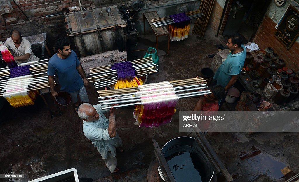 Pakistani workers dye thread at a factory in Lahore on November 20, 2012. The country is the world's fourth-largest producer of cloth and the industry accounts for 60 percent of export revenue according to official data. But shortages are heaping pressure on Pakistan's crippled and debt-ridden economy. AFP PHOTO/Arif ALI