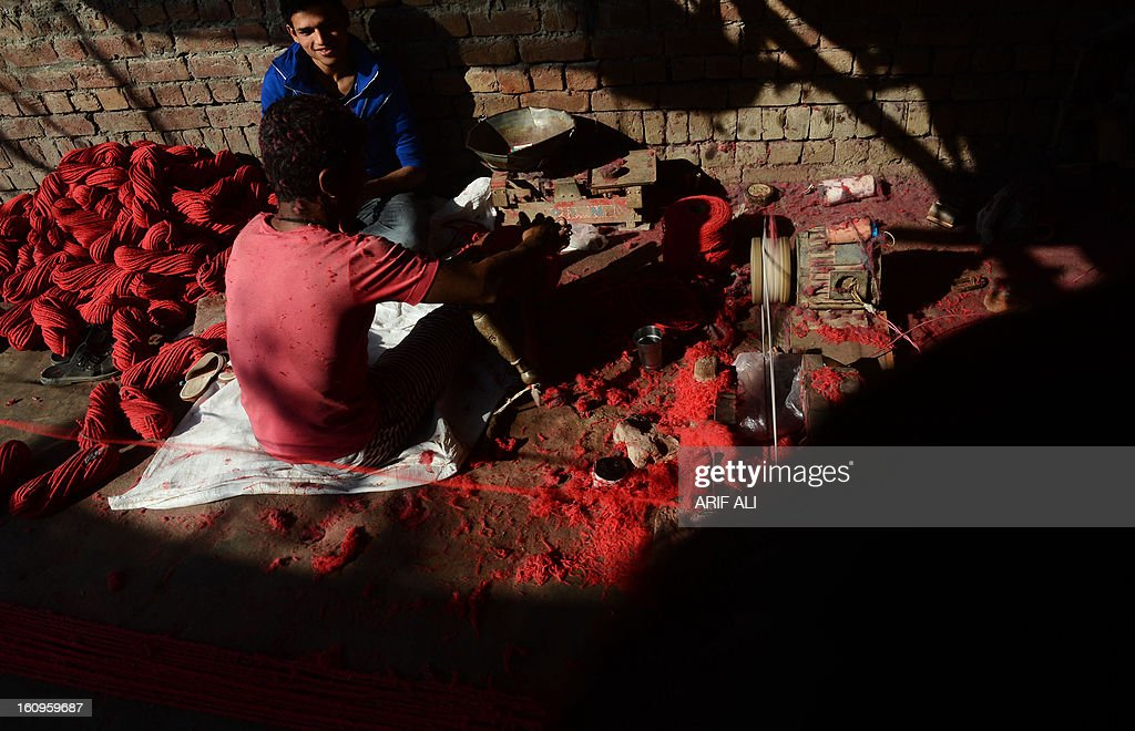 Pakistani workers dye thread at their roadside shop in Lahore on February 8, 2013. Pakistan's central bank on Friday kept its benchmark interest rate unchanged at 9.5 percent, as its foreign exchange reserves fell and GDP growth is expected to remain below four percent. AFP PHOTO/Arif ALI