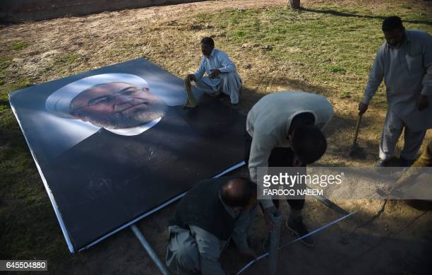 Pakistani workers from The Capital Development Authority carry a portrait of Iranian President Hassan Rouhani before installing it on a street in...