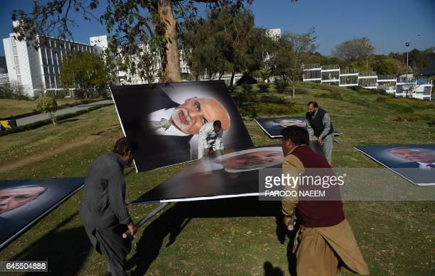 Pakistani workers from The Capital Development Authority carry portraits of Iranian President Hassan Rouhani and Afghan President Ashraf Ghani before...