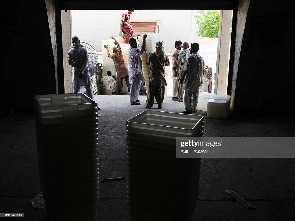 Pakistani workers load ballot boxes onto a truck before being transported to polling stations for the forthcoming parliamentary elections, in Karachi on May 6, 2013. Pakistan will elect its new government for the next five years in polls on May 11. The election of the national and four provincial assemblies will mark the first time a civilian government has completed a full term and handed over to another, in a country that has been ruled by the military for half its existence.