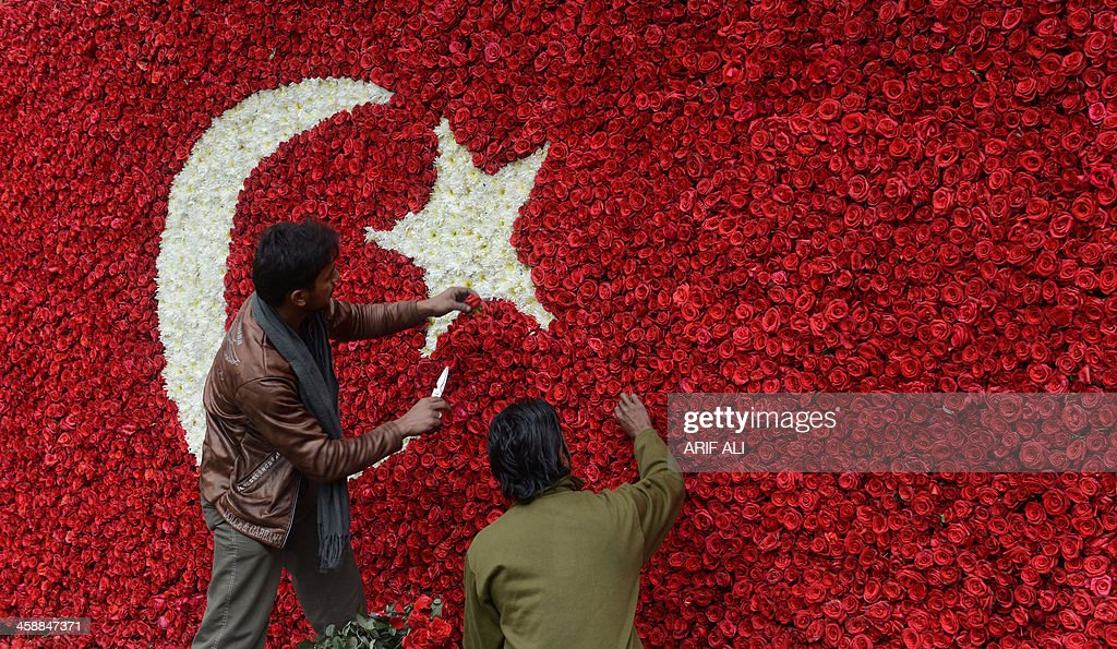 Pakistani workers make final touches to a Turkish flag made from rose petals ahead of a visit by Turkish Prime Minister Recep Tayyip Erdogan in Lahore on December 22, 2013. Erdogan is scheduled to pay a two-day official visit to Pakistan from December 23, to discuss economic cooperation between the two countries. AFP PHOTO/Arif ALI
