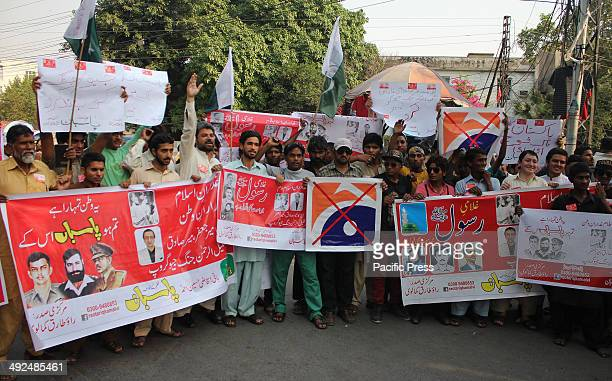 Pakistani workers of Religious party shout slogans during burning the LOGO of a famous TV channel Geo News in Lahore Pakistan The Geo programme Utho...