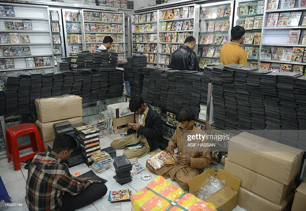Pakistani workers pack film DVDs at a video shop in Karachi on January 29, 2013. Pakistani movie distributors and TV stations are boycotting an Oscar-nominated film about the hunt for Osama bin Laden and popular US dramas to avoid offending sensibilities or sparking a violent backlash. AFP PHOTO/ Asif HASSAN