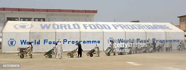 Pakistani workers prepare relief supplies for distribution to internally displaced Pakistani civilians fleeing a military operation against Taliban...