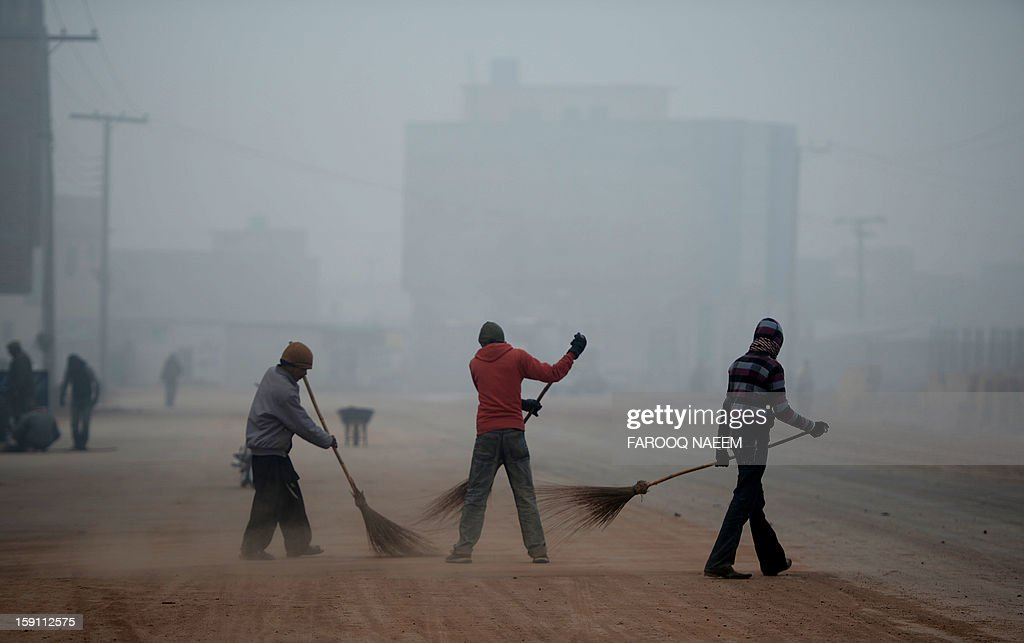 Pakistani workers sweep the road during a foggy morning in Islamabad on January 8, 2012. The fog has also disrupted flight schedules at the Islamabad airport and four Islamabad-bound flights from Dubai and Afghanistan were diverted to Lahore. AFP PHOTO/Farooq NAEEM