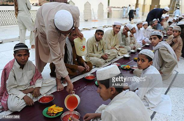 Pakistani youth arrange food before breaking their fast in Peshawar on July 21 on the first day of Muslims fasting month of Ramadan Muslims fasting...