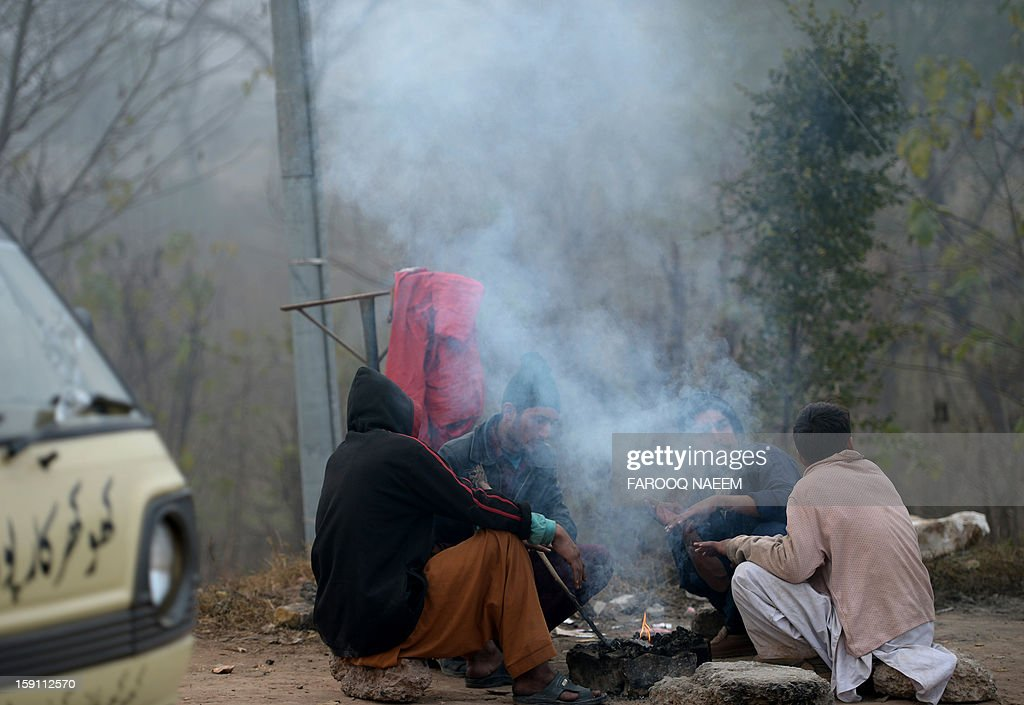 Pakistani youth gather around fire to warm themselves during a foggy morning in Islamabad on January 8, 2012. The fog has also disrupted flight schedules at the Islamabad airport and four Islamabad-bound flights from Dubai and Afghanistan were diverted to Lahore. AFP PHOTO/Farooq NAEEM