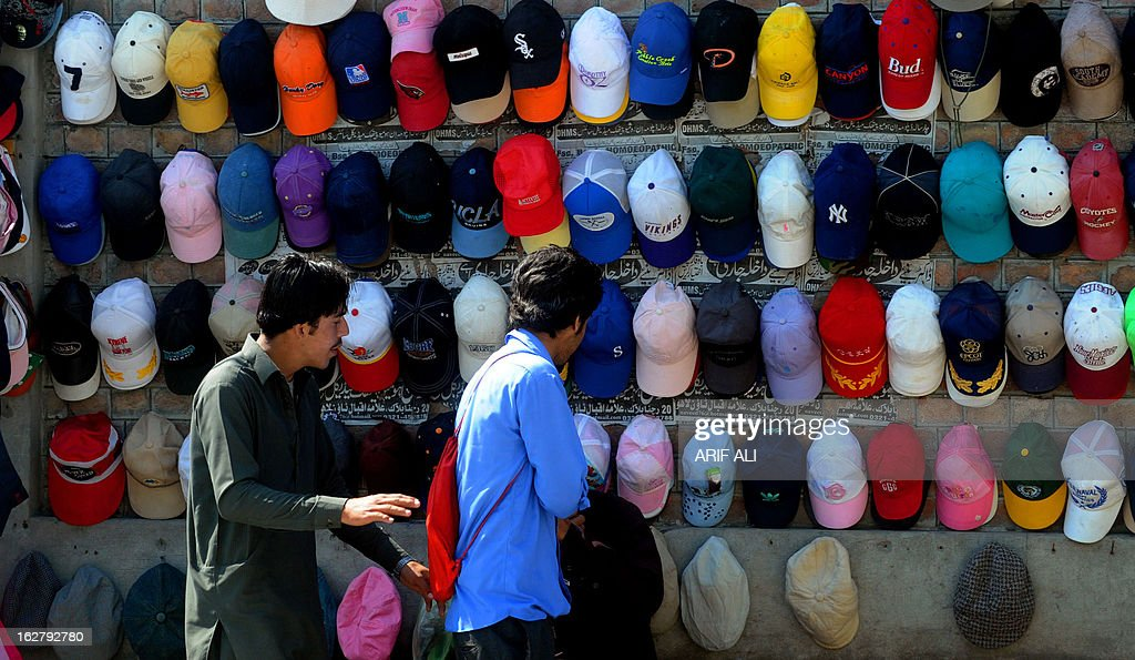 Pakistani youth look at caps on a roadside stall in Lahore on February 27, 2013. Food inflation dropped to 5.3 percent and non-food inflation to 8.1 percent. AFP PHOTO/ Arif ALI