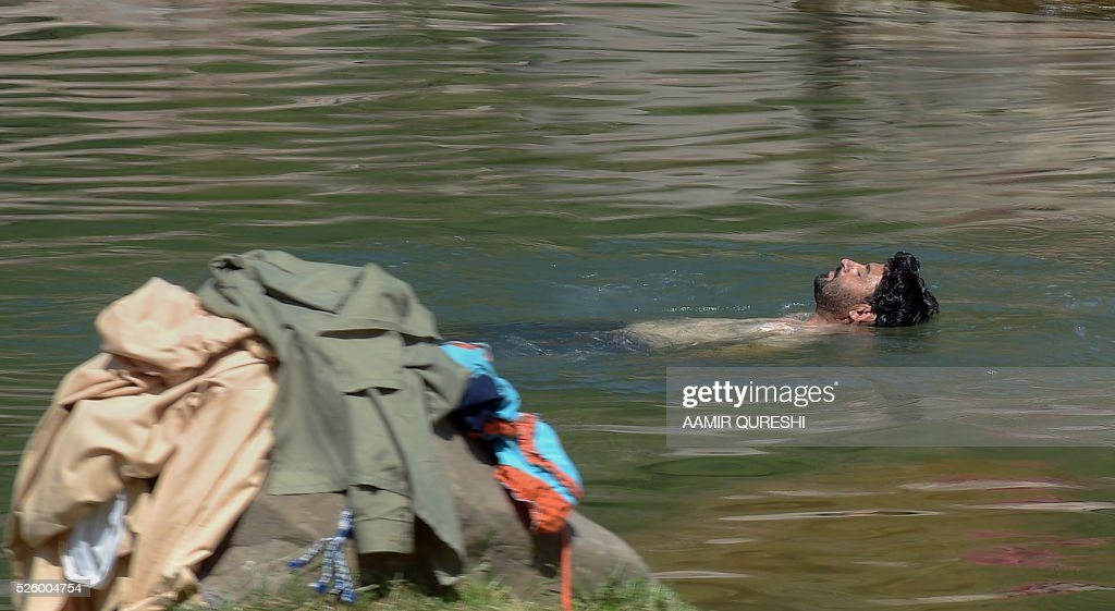 A Pakistani youth swims in a stream during hot weather on the outskirts of Islamabad on April 29, 2016. Pakistan's Meteorological Department has forecast hot and dry weather in most parts of the country with the highest temperatures recorded at 41 celsius in the southern Sindh province. / AFP / AAMIR