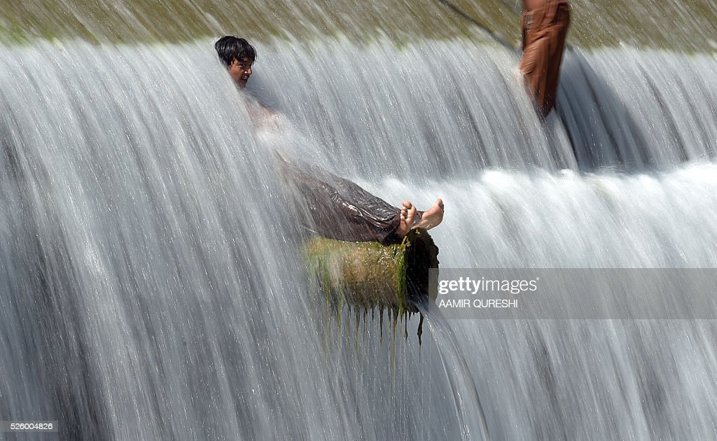 Pakistani youths cool off in a stream during hot weather on the outskirts of Islamabad on April 29, 2016. Pakistan's Meteorological Department has forecast hot and dry weather in most parts of the country with the highest temperatures recorded at 41 celsius in the southern Sindh province. / AFP / AAMIR