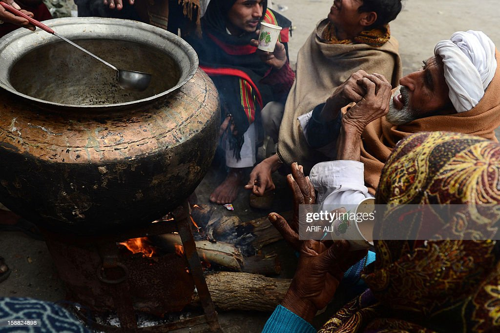 Pakistanis drink tea at a roadside during a cold and foggy morning in Lahore on December 31, 2012. Ongoing foggy weather in Punjab and other parts of the country has badly affected flight and rail schedules. AFP PHOTO/ARIF ALI