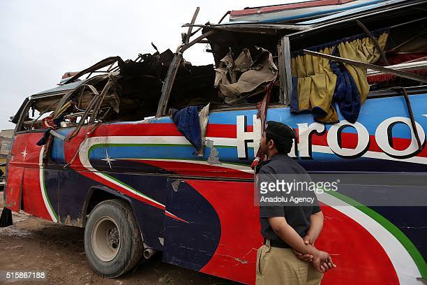 Pakistanis inspect a destroyed bus after a bomb blast in Peshawar on March 16 2016 At least 15 people were killed and 25 others wounded when a bomb...