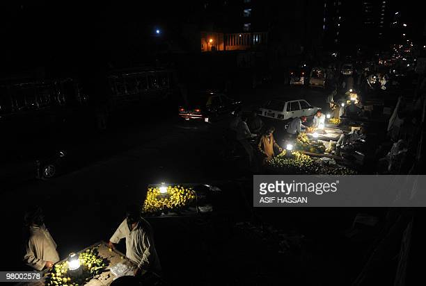 Pakistanis purchase fruit from roadside vendors at Empress Market in Karachi late March 21 2010 AFP PHOTO/ ASIF HASSAN