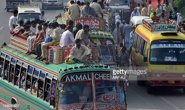 Pakistanis ride on the roof of an overcrowded bus as they return to their hometowns for the Eid alFitr festival in Lahore on August 30 2011 Bus and...