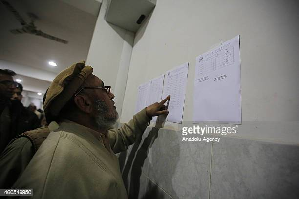 Pakistanis search for the names of their injured relatives from a list hung on the wall at Lady Reading Hospital where the casualties of Taliban...