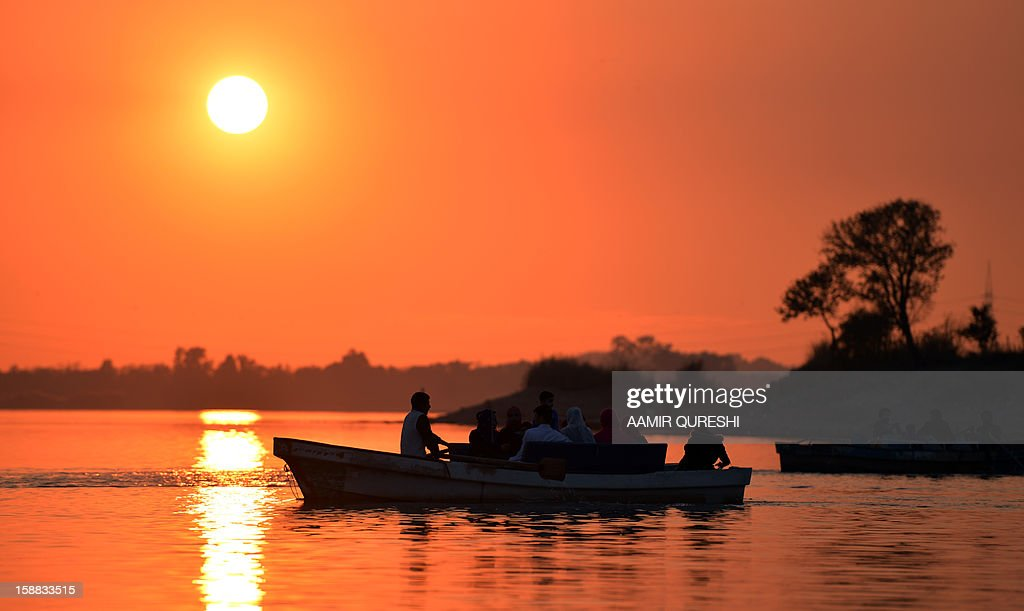 Pakistanis tourists ride on boats during the last sunset of 2012 at a lake view point in Islamabad on December 31, 2012. Sydney will kick off a wave of dazzling firework displays welcoming in 2013, from Dubai to Moscow and London, with long-isolated Yangon joining the global pyrotechnics for the first time. AFP PHOTO/ Aamir QURESHI