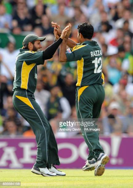 Pakistan's Abdul Razzaq celebrates with teammate Shahid Afridi after taking the wicket of New Zealand's Brendon McCullum during the ICC World...