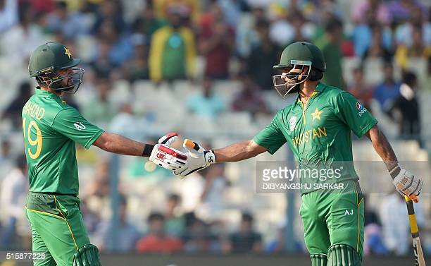 Pakistan's Ahmed Shehzad celebrates with teammate Mohammad Hafeezafter scoring a halfcentury during the World T20 cricket tournament match between...
