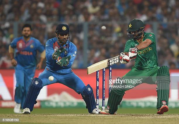 Pakistan's Ahmed Shehzad plays a shot as India's captain Mahendra Singh Dhoni looks on during the World T20 cricket tournament match between India...