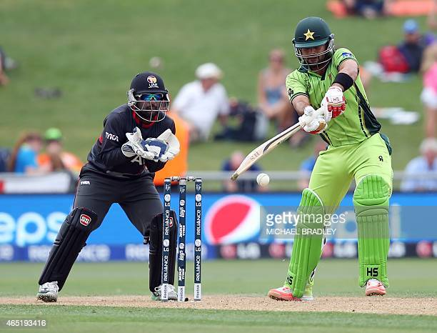 Pakistan's Ahmed Shehzad plays a shot as United Arab Emirates wicketkeeper Swapnil Patil looks on during the Pool B Cricket World Cup match between...