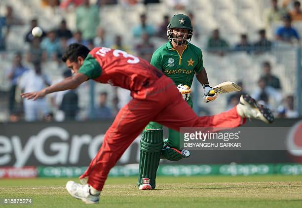 Pakistan's Ahmed Shehzad watches the ball as he plays a shot while Bangladesh's Taskin Ahmed tries to field the ball during the World T20 cricket...