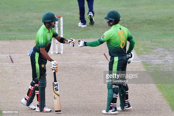 Pakistan's Babar Azam and Muhammad Hafeez gesture during the first one day international cricket match between Sri Lanka and Pakistan at Dubai...