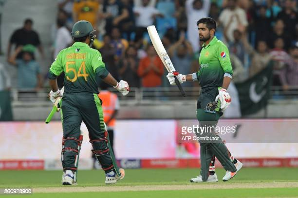 Pakistan's Babar Azam celebrates 100 runs with Pakistan's Sarfraz Ahmed during the first one day international cricket match between Sri Lanka and...