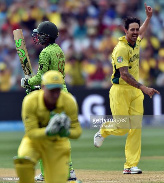 Pakistan's batsman Haris Sohail walks off the field as Australia's paceman Mitchell Johnson celebrates his wicket during the 2015 Cricket World Cup...