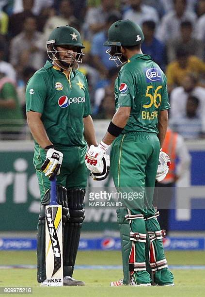 Pakistan's batsman Khalid Latif talks with his teammate Babar Azam during the first T20I match between Pakistan and the West Indies at the Dubai...